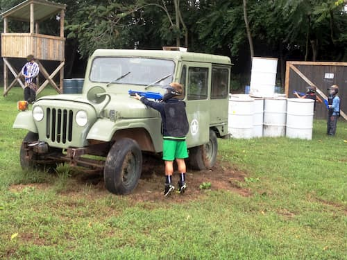 kid shooting gotcha low impact gun behind jeep