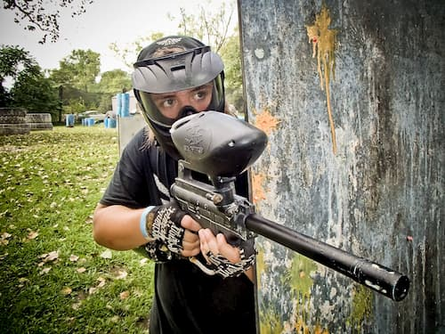 paintball player shooting from behind wall