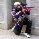 crouching paintball player shooting gun