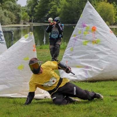 paintball player sliding behind bunker