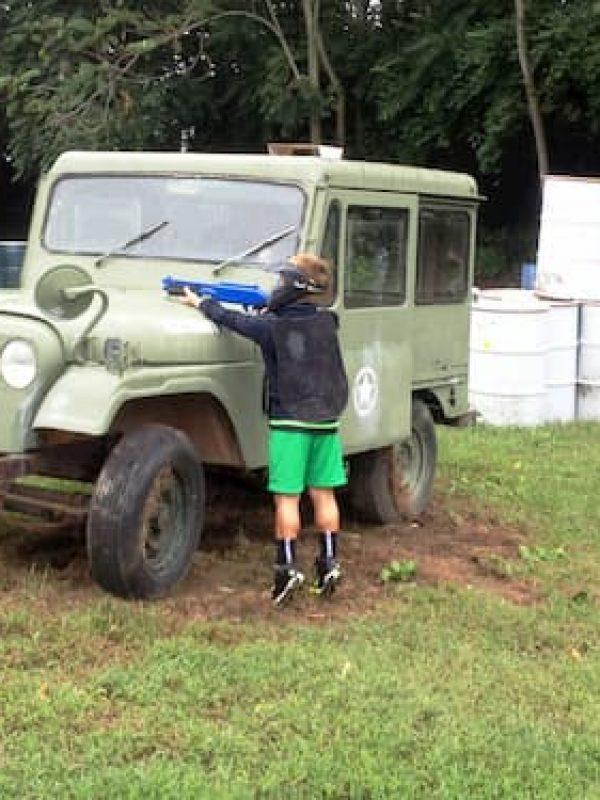 kid shooting gotcha low impact gun behind jeep