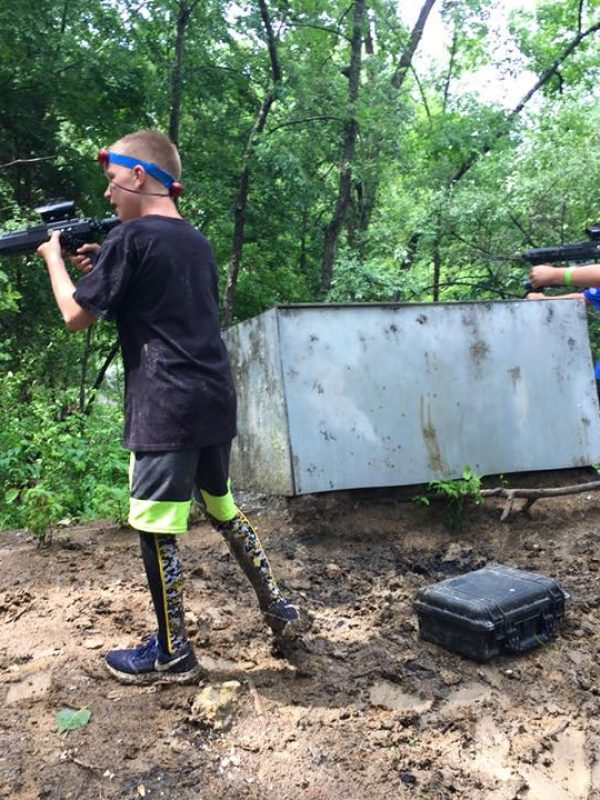 2 boys shooting airsoft guns in woods field