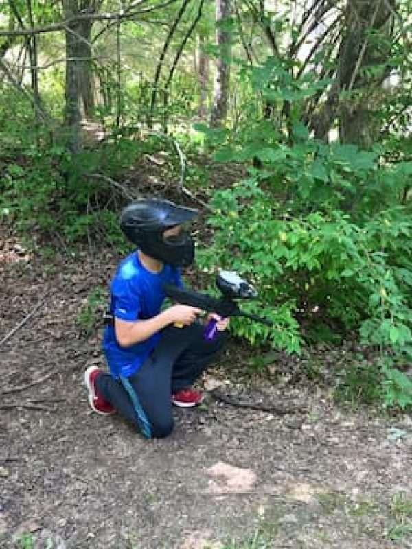 boy with low impact paintball gun crouching in woods