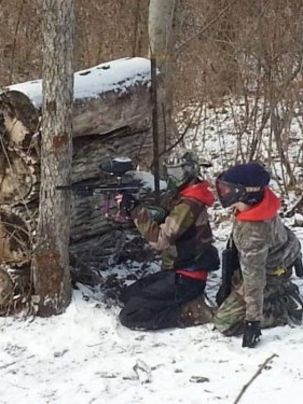 2 boys in snow shooting paintball gun from behind logs